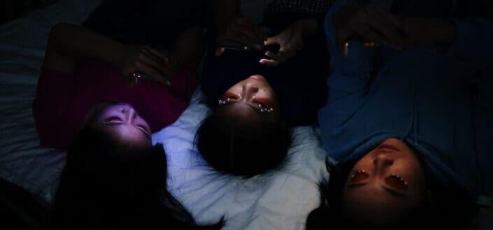 women lying at their bed at dark