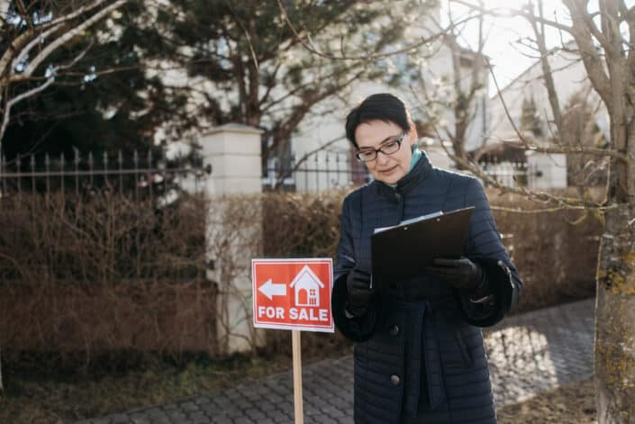 Woman holding contract for a house for sale.