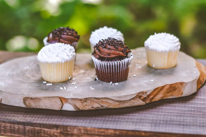 five cupcakes on wooden board