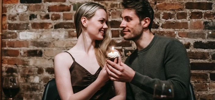 couple with cupcake celebrating in restaurant