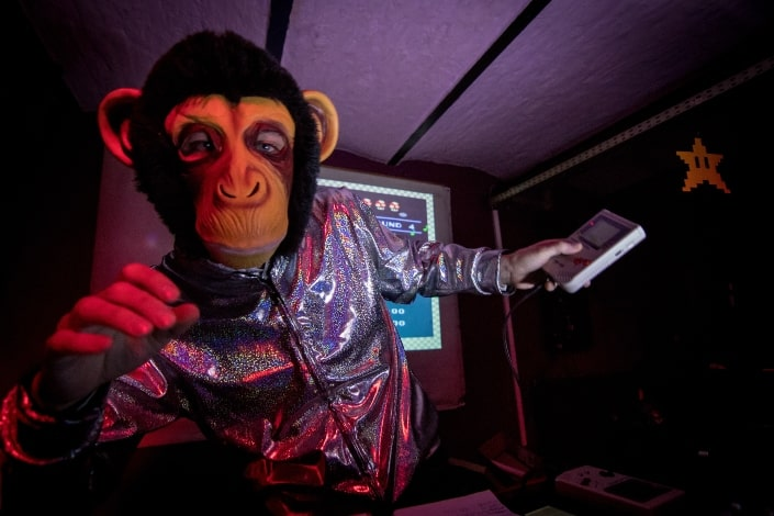 man dress as monkey and holding game boy