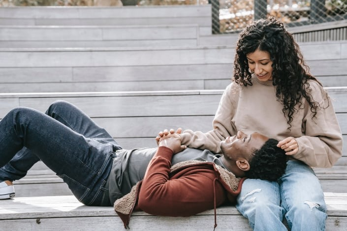 multiethnic couple holding hands on steps
