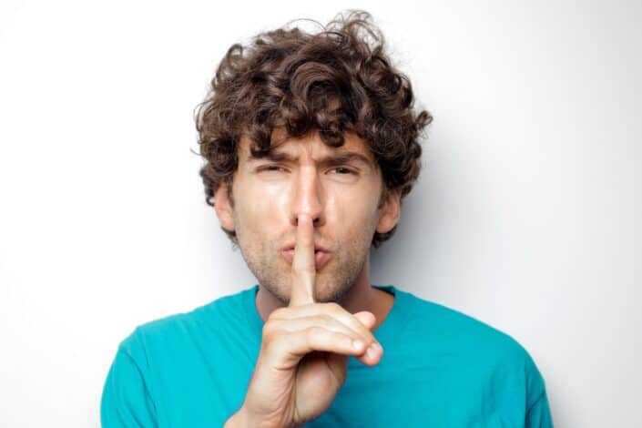 Curly haired man doing a hush sign