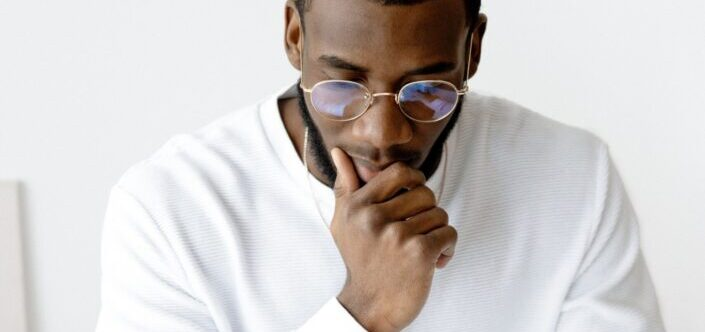 A man in eyeglasses on a deep thought
