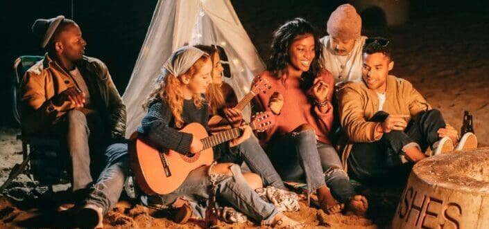 Group of friends on a camping singing with a guitar while gathered around their campfire
