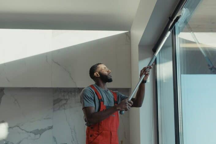 A man cleaning a window pane