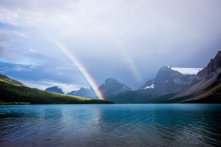 A rainbow over a lake through the mountains.