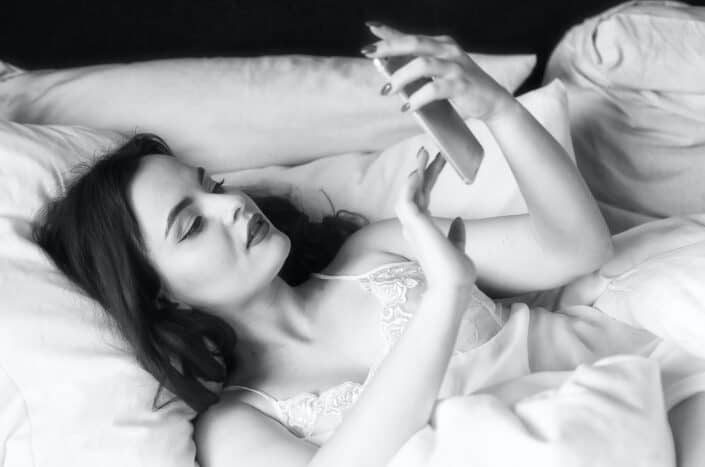 Woman reading a text message in her bed.