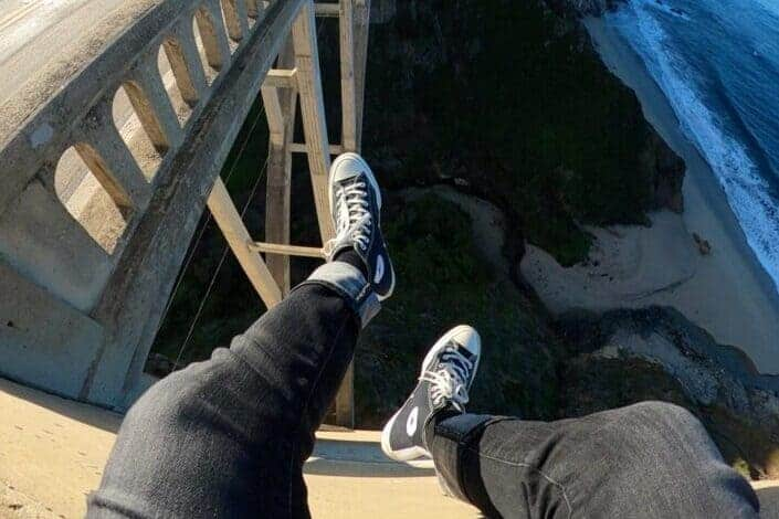Person sitting over the bridge railing