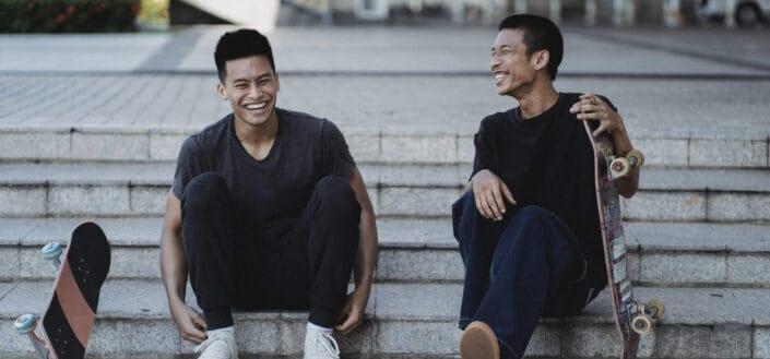 joyful men resting on street staircase with skateboard
