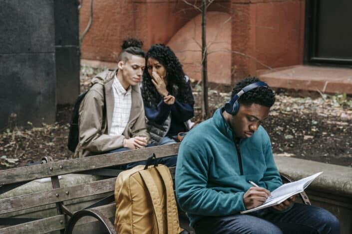 Multiethnic friends gossiping behind attentive classmate