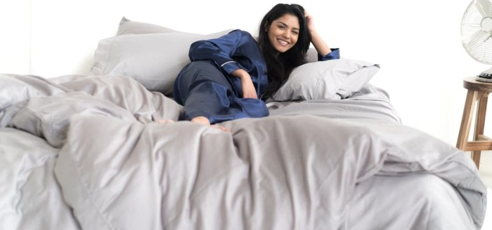 Happy woman laying comfortably at her bed.