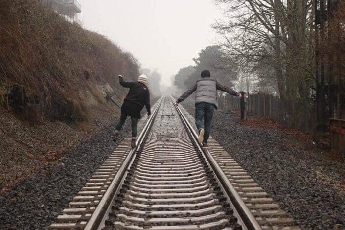 couple having fun trailing on the train rail.