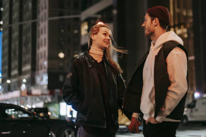 Couple holding hands and talking on the street