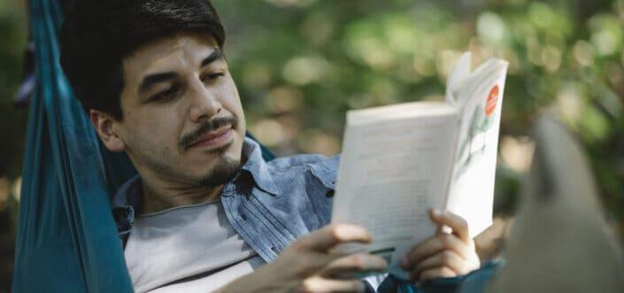 Man enjoys reading book while on a hammock.