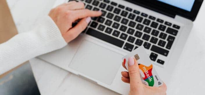 Person Holding credit card and using laptop.