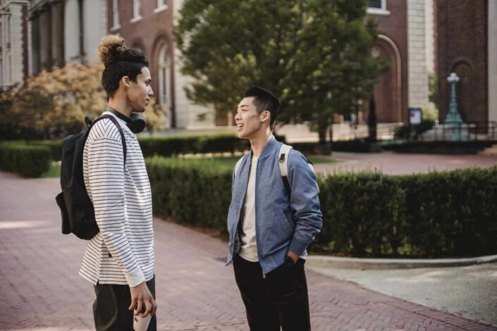 Cheerful multiethnic male friends chatting on street