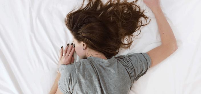 A woman appreciating her bed.