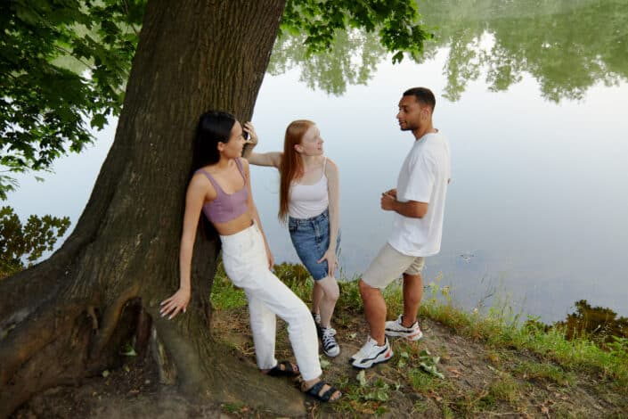 Two women friends chilling with a guy beneath a lake.