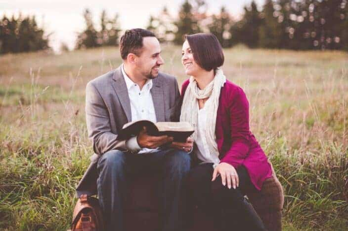 Couple reading book outside