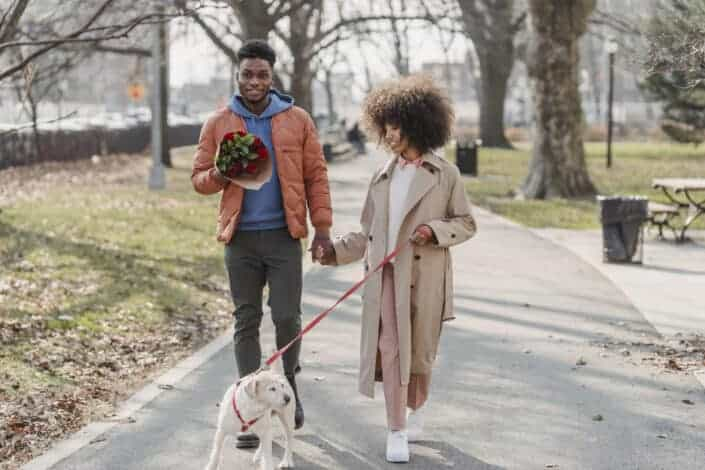 Couple walking outside with their pet