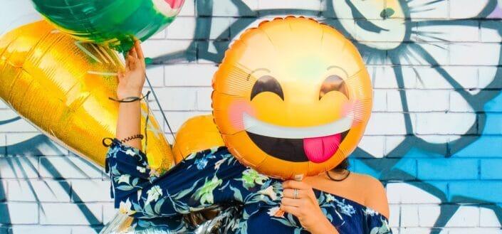 Girl holding balloon on her face