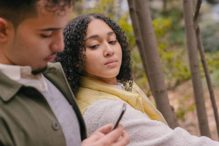 Hispanic man using smartphone while woman watching