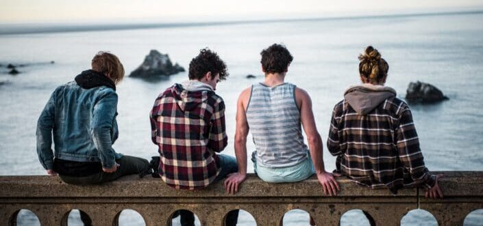 four people sitting on bench infront of sea