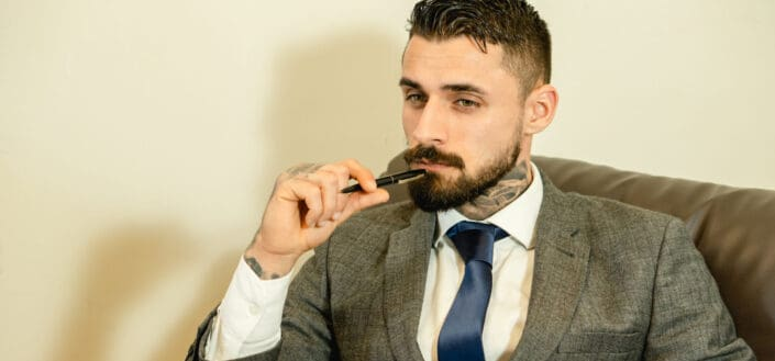 Man poking his chin with a pen