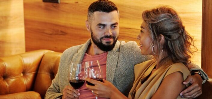 Couple talking and clinking glasses