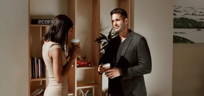 Man and woman in formal attires talking while having a cup coffee.
