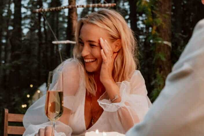 Woman giggling while holding glass of champagne