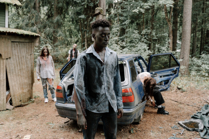 zombies walking by a ravaged car