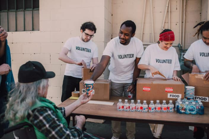 Group of volunteers giving food to homeless