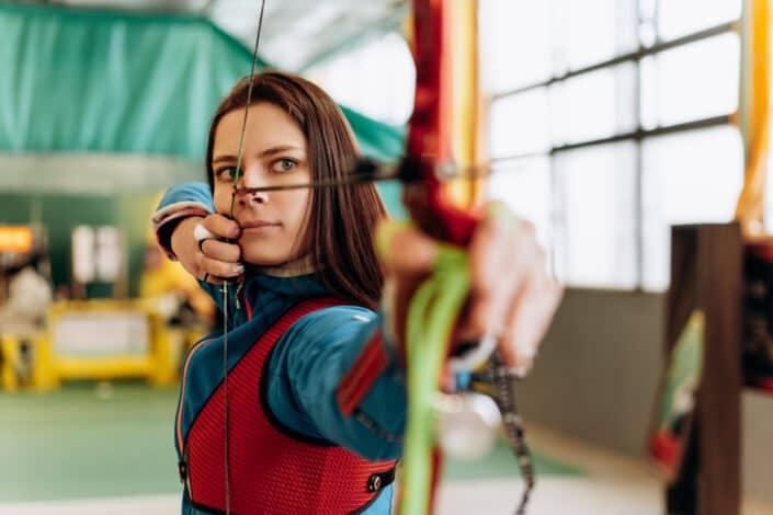 Woman gesturing to shoot an arrow