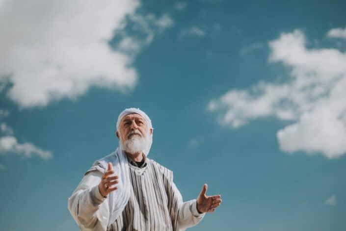 A old man gesturing like explaining something.
