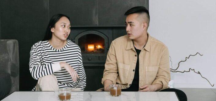 Couple talking beside a fireplace