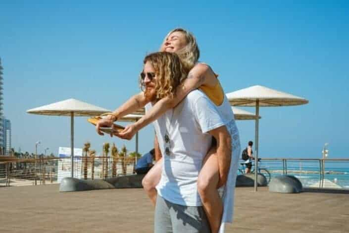 Man carrying his woman by the beach