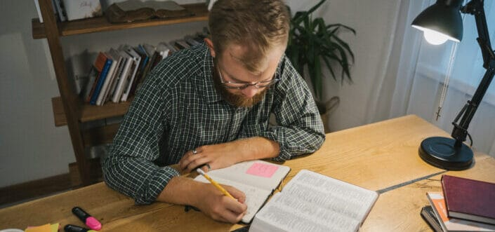 Man jotting down some biblical contents.