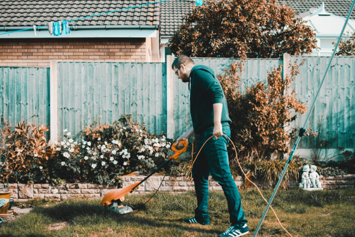 Man mowing the lawn of his backyard