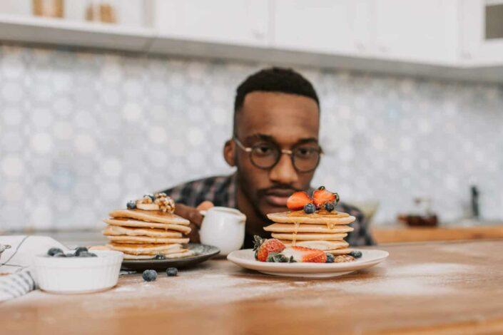 Man staring at a pile pancakes