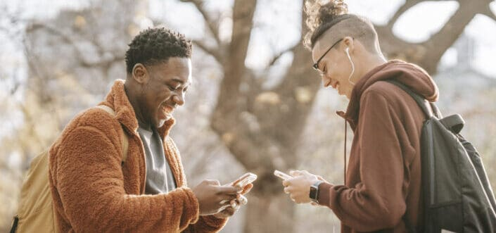 Men smiling while holding their phones