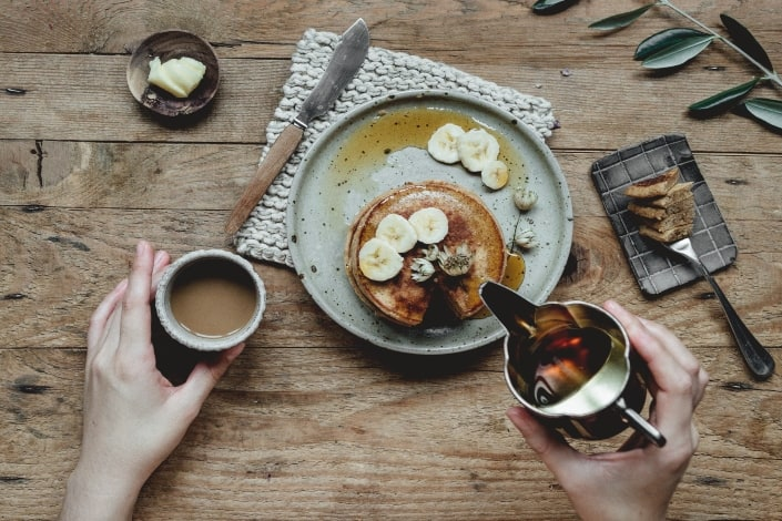 A breakfast set of pancake topped with banana and syrup