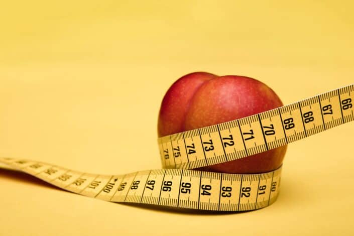 A red apple wrapped in a tape measure