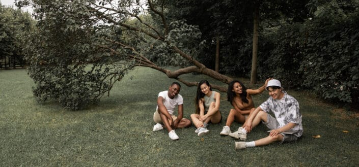 Four friends sitiing on a grass in a backyard while catching up