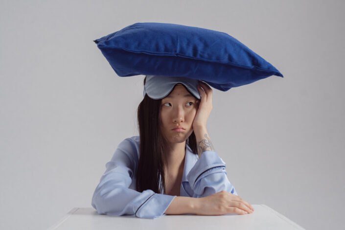 Woman in a sleeping outfit with pillow on her head