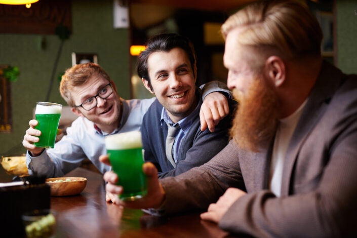 Three office people happily drinking a green alcoholic drink