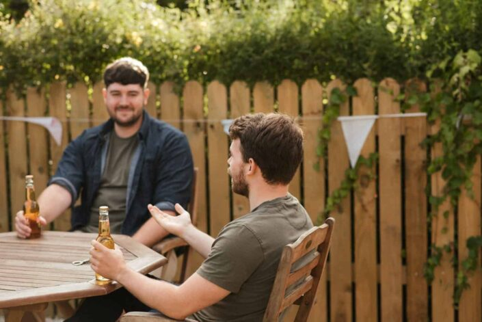 Two guys drinking beer on their garden while having a chat