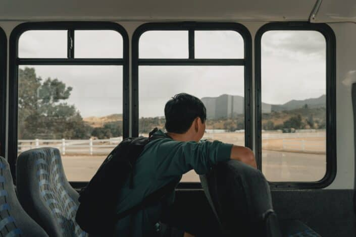 A young man staring outside the window bus