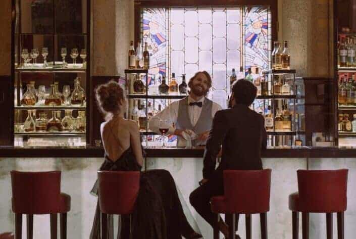Elegant couple with bartender on bar counter